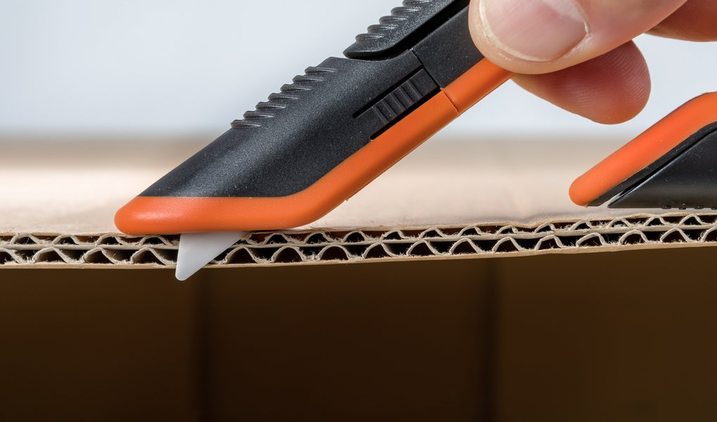 The Slice 10400 Manual Box Cutter, arguably the best tool to cut cardboard, shown with the blade exposed next to a cross-section of double-walled corrugated.