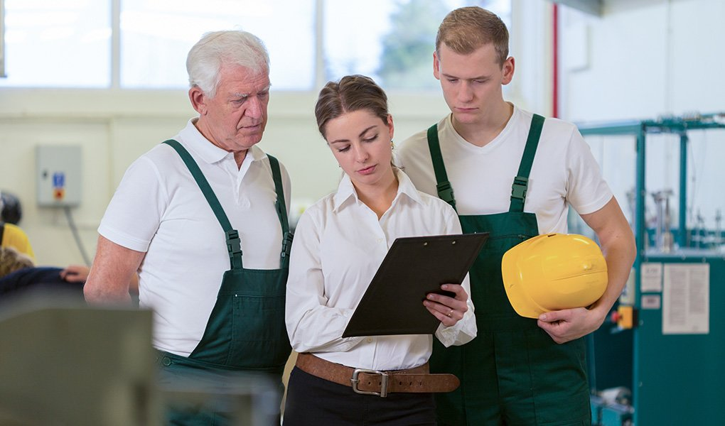 Woman in warehouse sharing protocol for health and safety of employees in the workplace with two male colleagues.