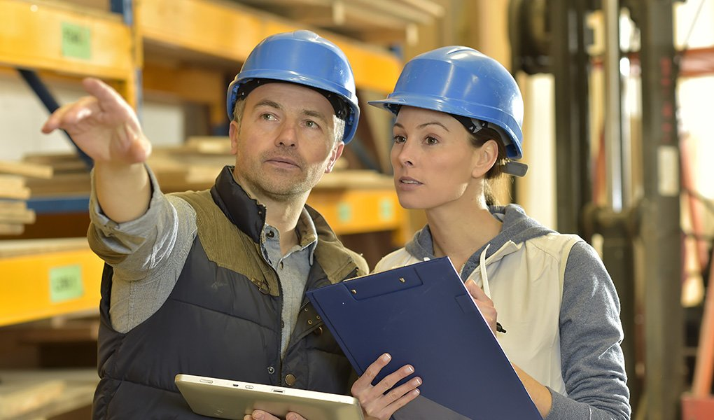 In a warehouse setting, a man holding a tablet points in the distance, and a woman holding a clipboard takes notes; both are wearing blue hardhats.