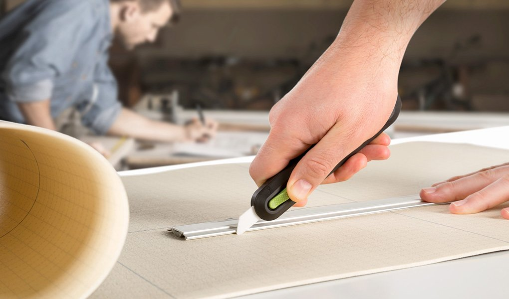 Hand using a utility knife, one of a number of industrial knives and blades.