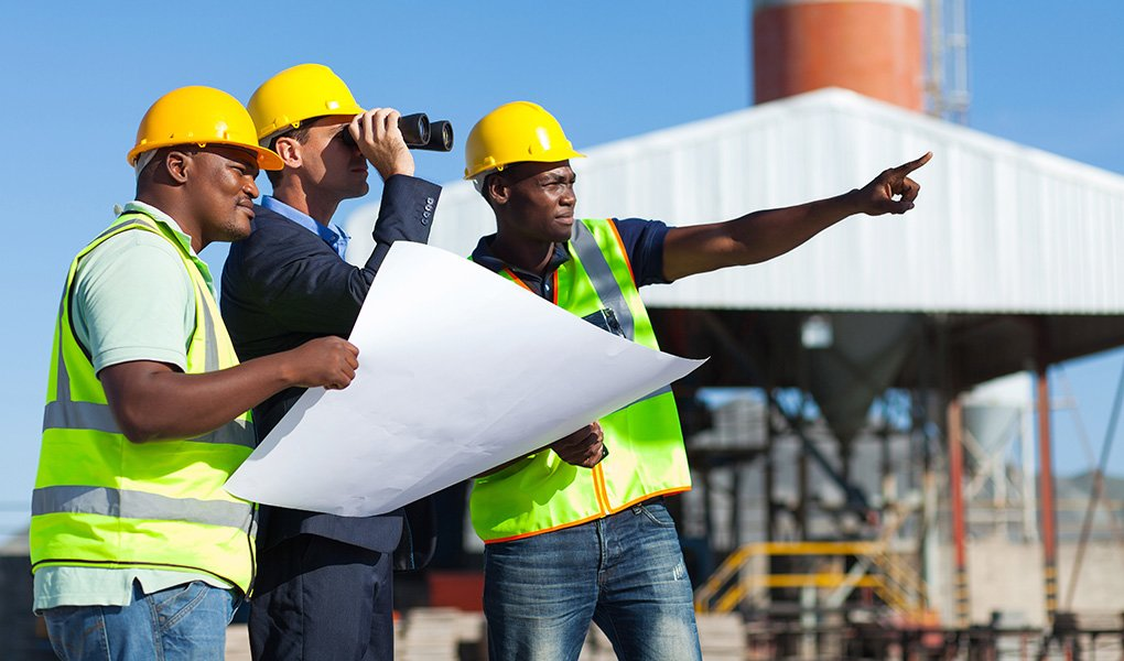 Three men in industrial safety supply gear at a construction site look into the distance.