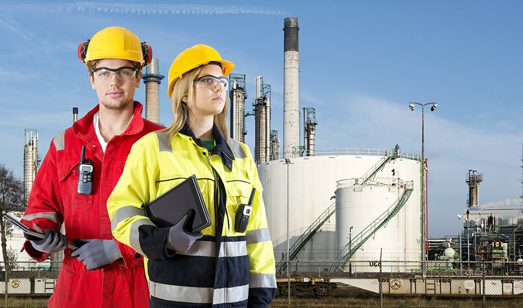 Man and woman wearing safety clothing, gloves, hard hats, and goggles in front of a petrochemical plant, demonstrating good industrial safety.