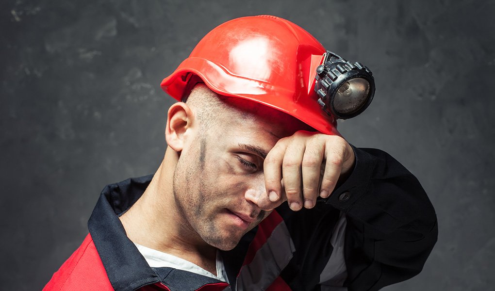 Headshot of man with dirty face wearing safety helmet with light and wiping forehead