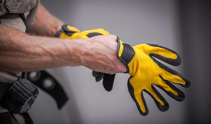 Close-up of man preventing hand injuries by putting on safety gloves.
