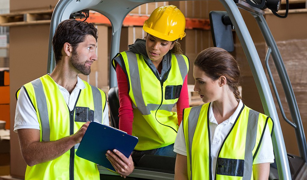 Man with clipboard discussing safety training topics with two women for their next toolbox talk.