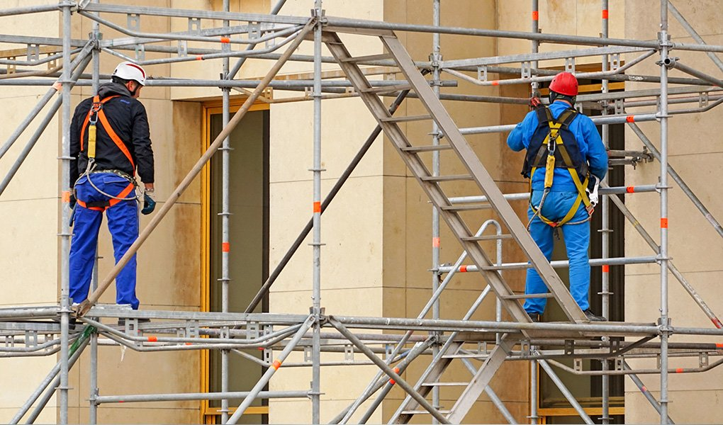 Two men in safety gear working on scaffolding