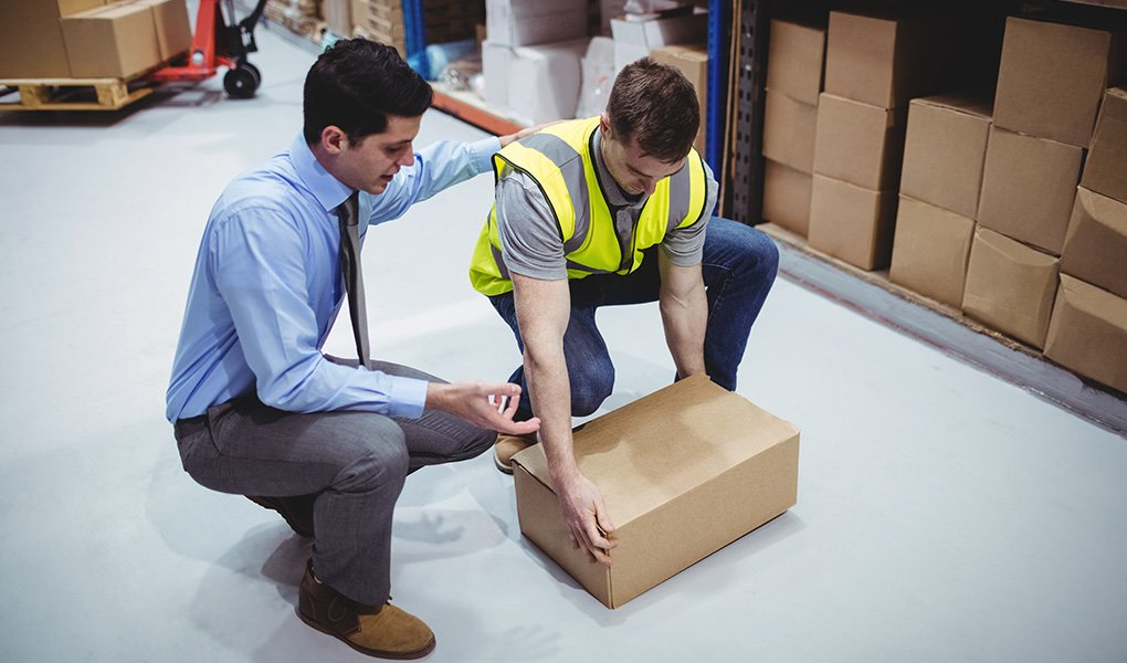 Supervisor coaching warehouse worker to lift boxes correctly